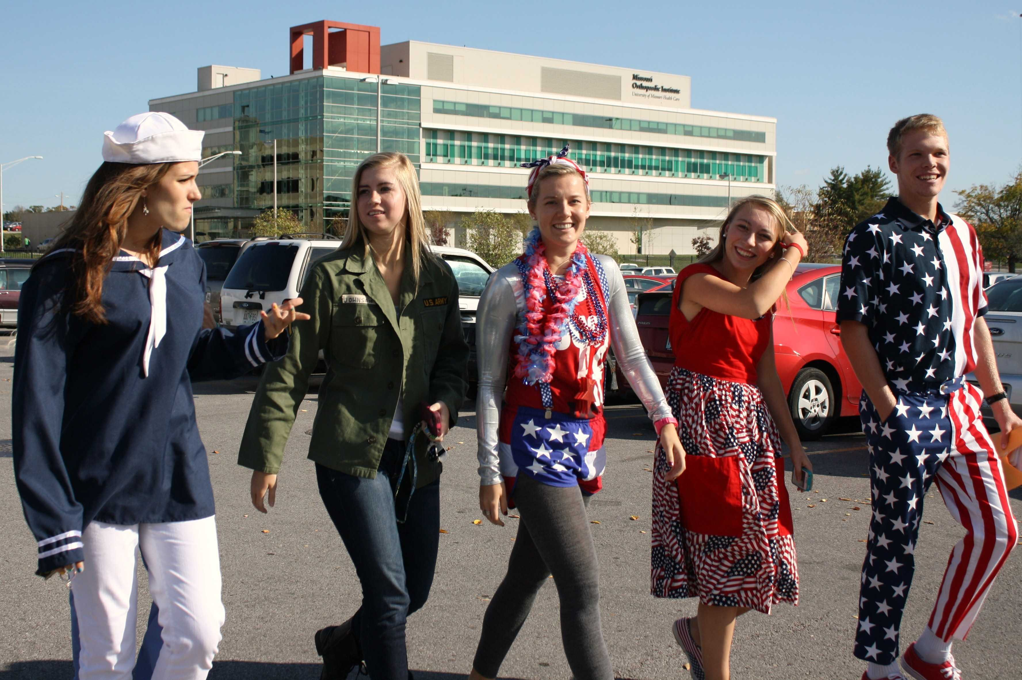 Homecoming candidates Morgan Widhalm (far left), Sydney Strong (left center), Taylor Wilson (center), Annie Rumpf (center right), and homecoming escort Alex Jones (far right) head into the Veterans' Hospital, bringing their vibrant colors and patriotism with them.