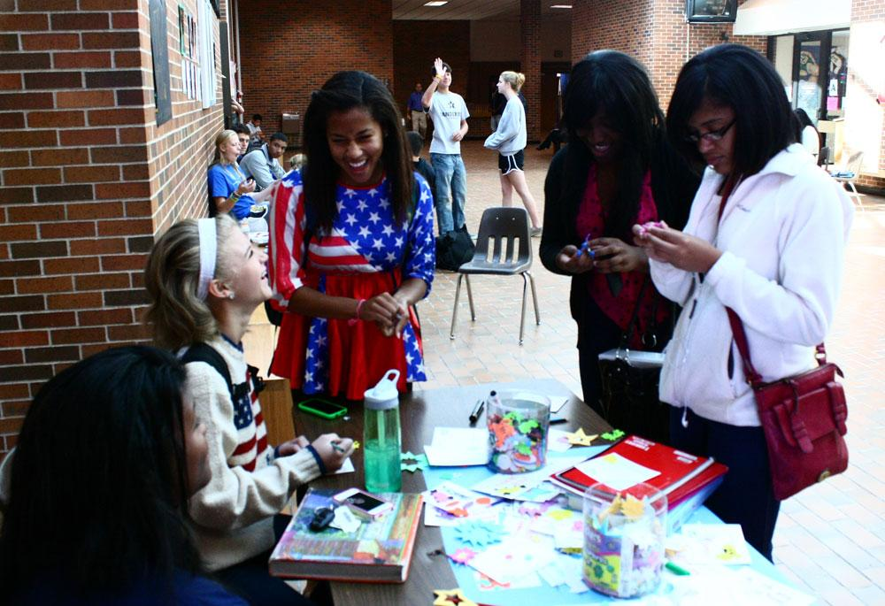 From left to right: Queen candidates seniors Christina Young, Morgan Bumby and Olivia Mends help students create cards for veterans. Photo by Stazi Prost