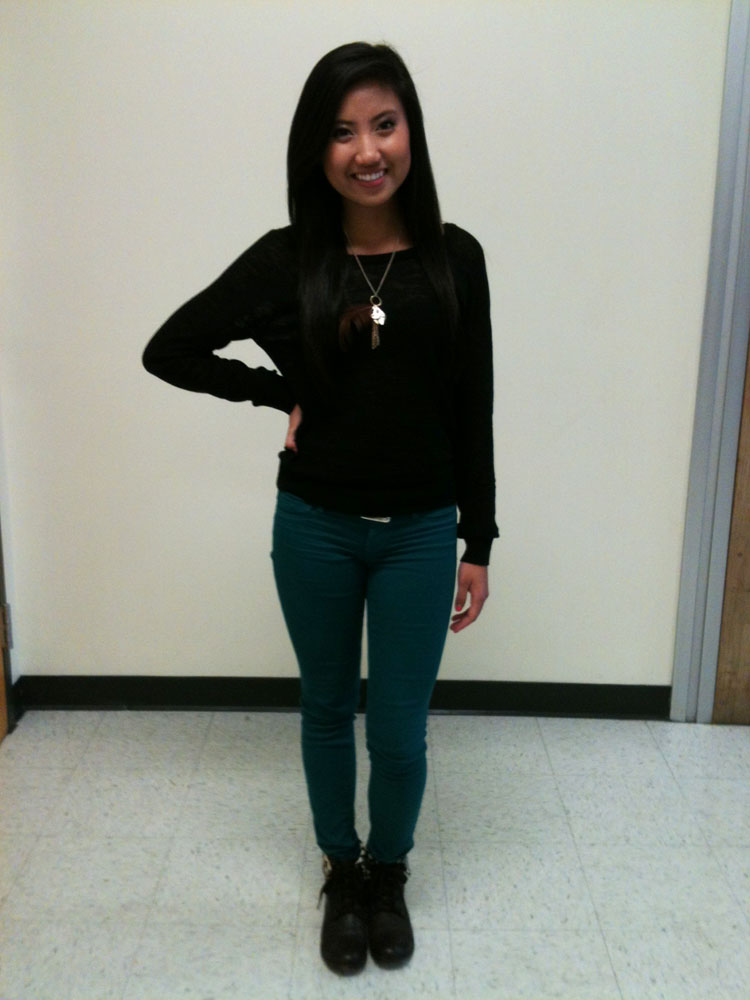 Ngo sports a pair of teal skinny jeans, a black top and a feathered necklace with gold accents. Photo by Lauren Puckett