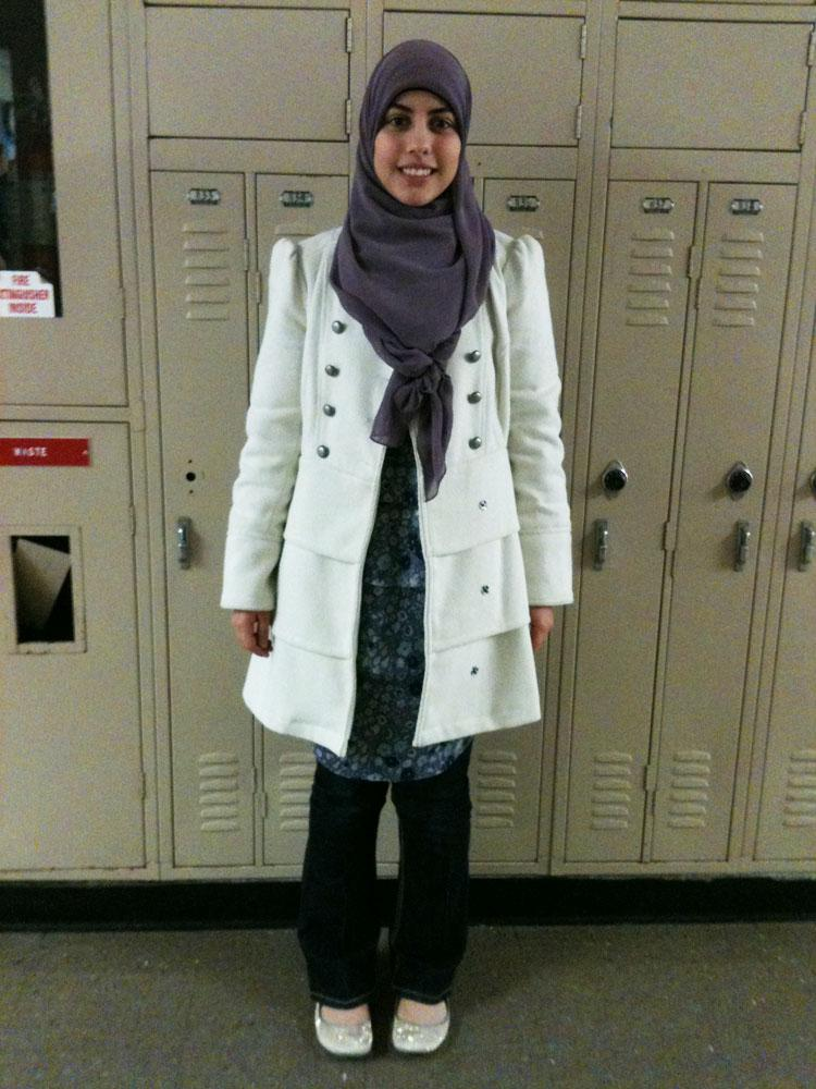 Senior Duha Shebib sports a white pea coat with a purple hijab and floral shirt. Photo by Lauren Puckett