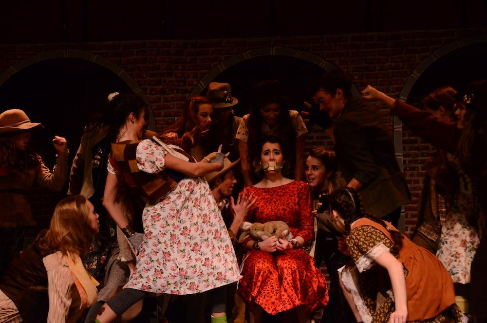 """Megan Kelly as Hope Cladwell, surrounded by the Poor Chorus during the song  """"Snuff That Girl"""" in """"Urinetown: The Musical."""" Junior Megan Kelly, who plays Hope Gladwell, falls in love with Bobby Stong, played by senior Ian Meyer, not pictured. Photo by Laurel Critchfield"""