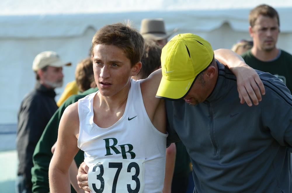 RBHS Cross Country coach Neil Blackburn leads Zach Cook away from the finish line at today's state cross country championships. Cook collapsed just after the three mile mark, picked himself up, and walked the race's final hundred meters to the crowd's applause. Photo by Asa Lory