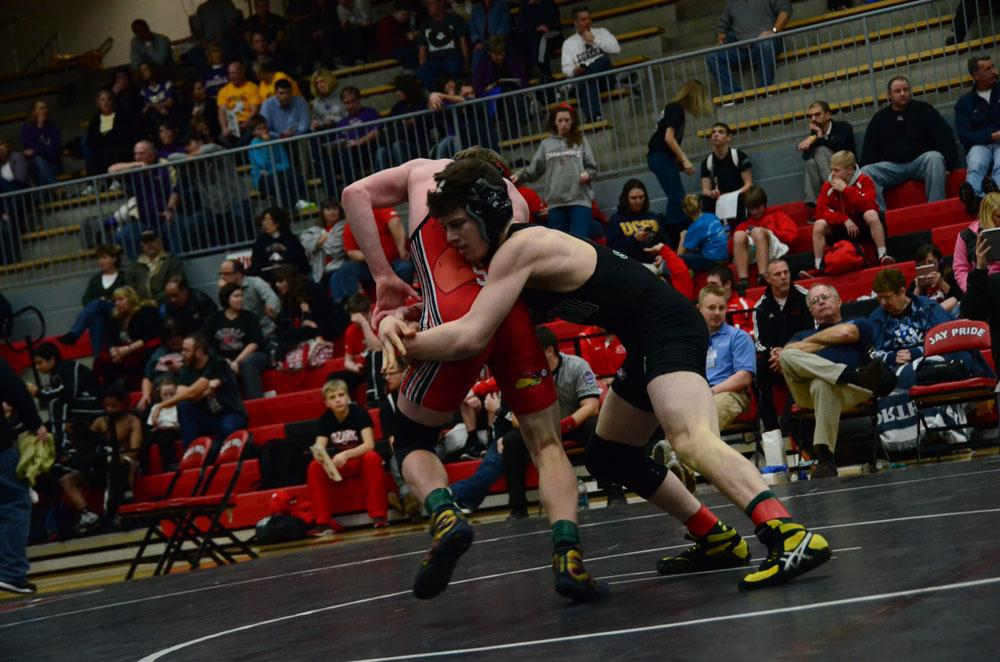 A Jefferson City Jay in the 126 weight class tries to score a point on an escape against opponent, junior Quinn Smith.