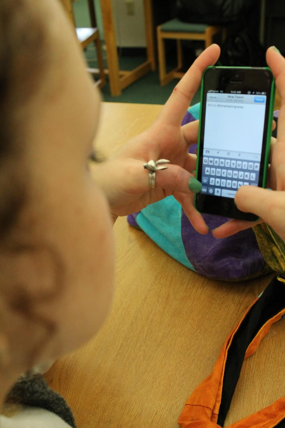 Junior Mariah Brady looks at her phone while she prepares to send a tweet. She allows people to view her sporadic personality through her Twitter profile. Photo by Maddy Jones