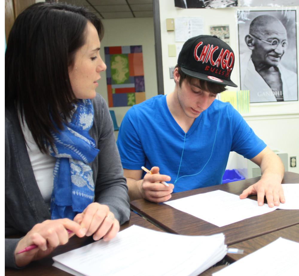 Mathematics teacher Amanda Dablemont assists junior Tim Stewart on a worksheet. She works with him one-on-one to solve a problem. Photo by Luke Wyrick