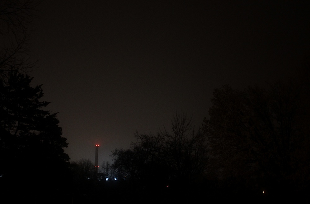Nine o'clock. I take a shortcut through my old elementary school playground. Even here, the smokestacks watch through the mist. They're a comforting sight though. Ever since I was little, I've felt safe anywhere in the city, as long as I can see the towers. If I can see the eyes blinking on and off, on and off slowly, I know I can find my way home.