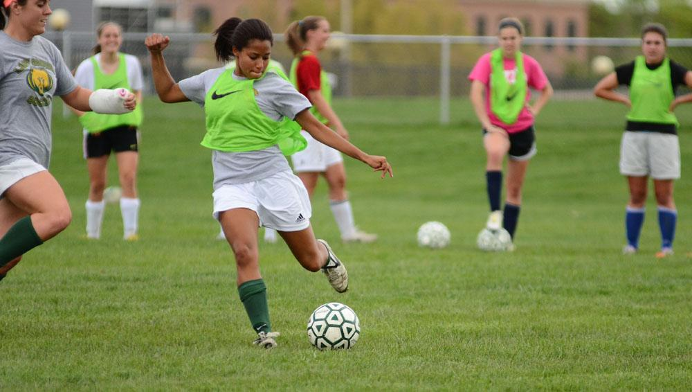 Senior Olivia Mends strikes the ball during a scrimmage in preparation for the district tournament. Mends played mid-fielder and forward for the varsity girls soccer team this season. Photo by Aniqa Rahman