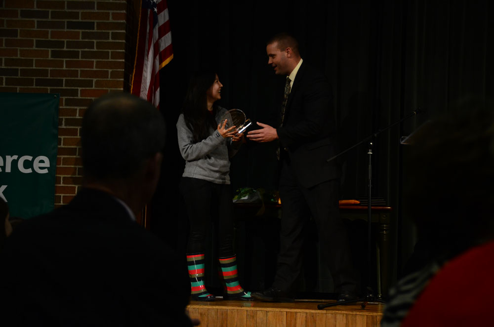 Senior Nomin-Erdene Jagdagdorj receives the Wayne Walker award from principal Mark Maus at the Flashback assembly. Jagdagdorj's efforts in journalism, volunteering, and publishing were reasons Maus cited for the award. Photo by Mikaela Acton