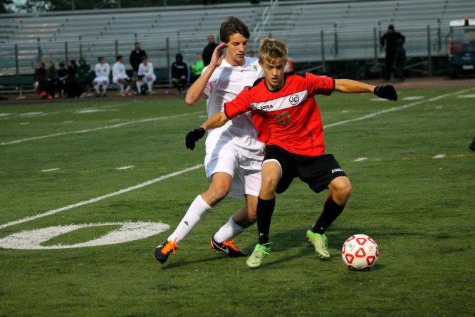Connor Blitz, grade 11, defends the opposing team member from turning the ball around and heading for the goal.