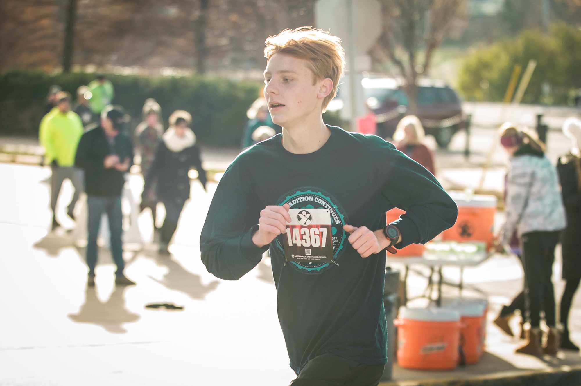 Senior Kevin Kiehne passes the aid station approximately two and half miles into the Turkey Trax Run on Nov. 23. Kiehne finished tenth overall out of the 1,282 participants this year. Photo by Yousuf El-Jayyousi