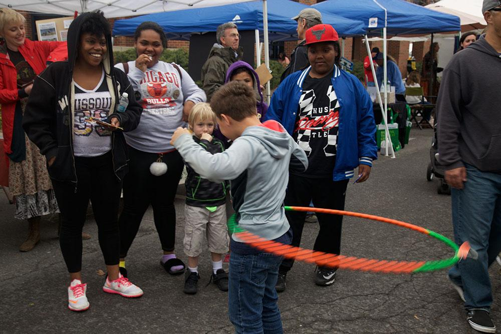 Community members whoop and cheer for young hula hoopers on the Broadway streets.