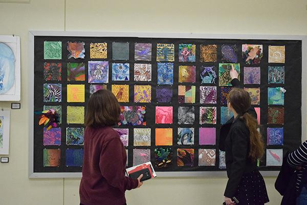 Students analyze their peers' artwork on display at the art show.