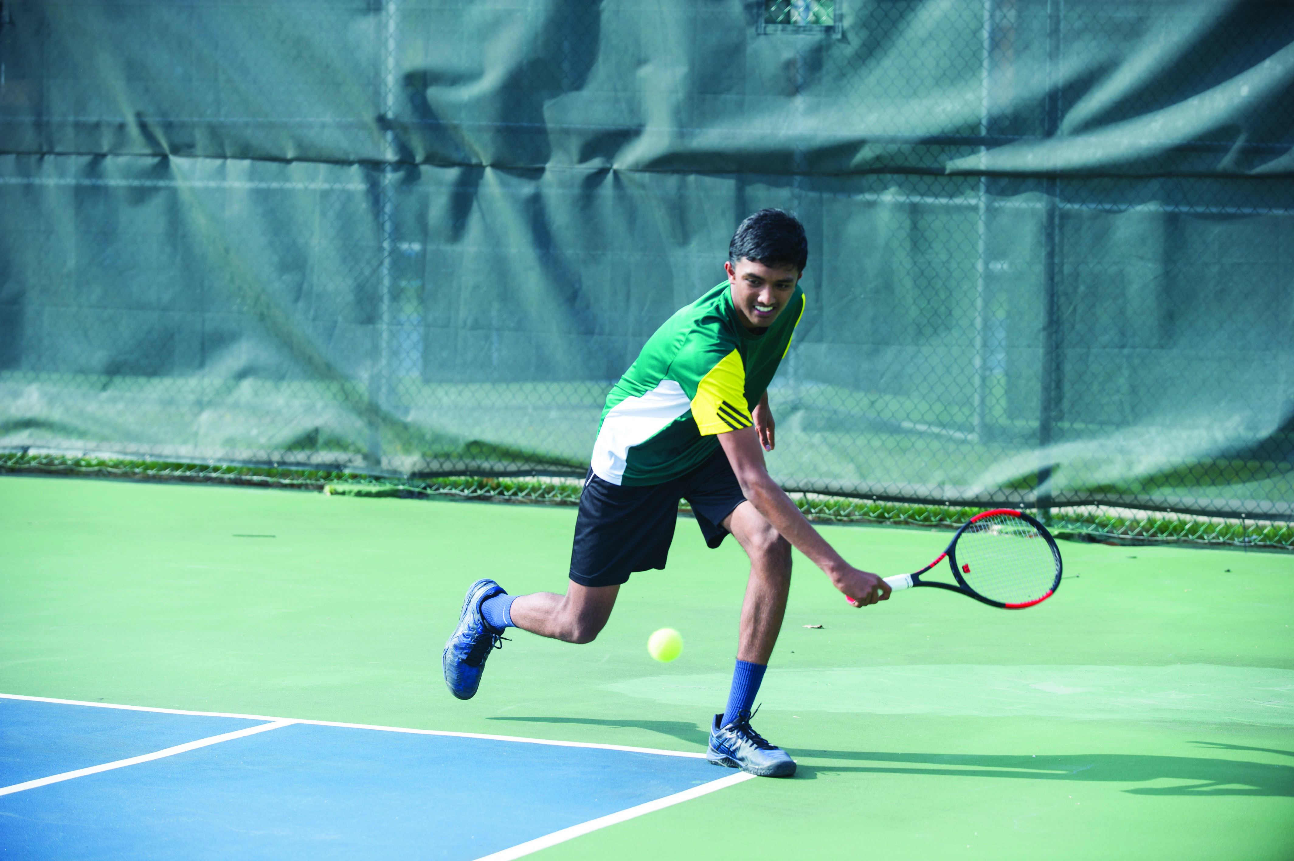 Junior Kavin Anand prepares to hit the ball with a back hand on April 26 against the Kewpies (9-0). The Bruins compete in individual districts May 12.