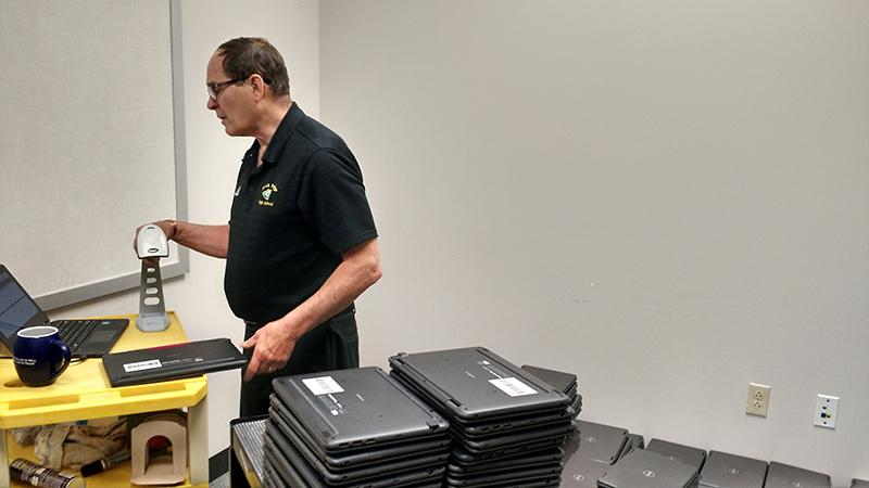 Dennis Murphy checks in all the laptops that have been turned in so far. Photo by Isaac Parrish.