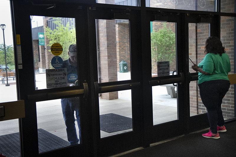 Custodial staff works with administrative staff to get the main commons doors to lock successfully during modified lockdown, Sept. 7. Photo by Camryn DeVore