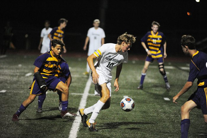 Flink turns away from a pile of Kewpies around him. Throughout the game, Flink slid many passes through the HHS defense. Flink has been a controlling factor of the Bruins' midfield this season. Photo by Allie Pigg.
