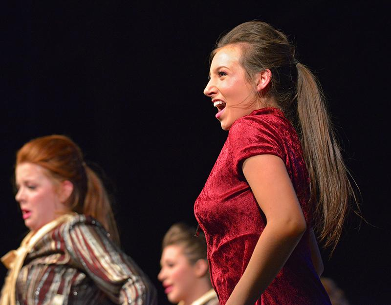 Junior Caroline Costa sings out during the Satin n' Lace performance. Because Costa is a member of both RBHS show choirs, this was only her first of many times on stage for the evening.