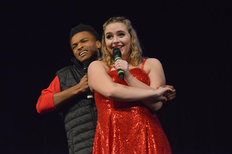 Two Battalion singers pose together during their duet. After a quick costume change, the Battle show choir returned to the stage in sparkly red outfits, singing about love.