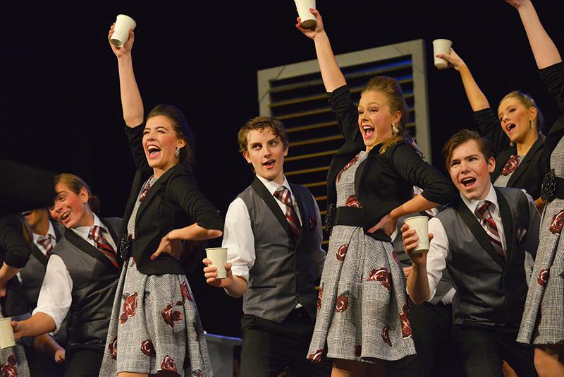 City Lights raises their cups of coffee during their show. This portion of the performance was all about a work day in an office, and how they could not get through it without a cup of black coffee.