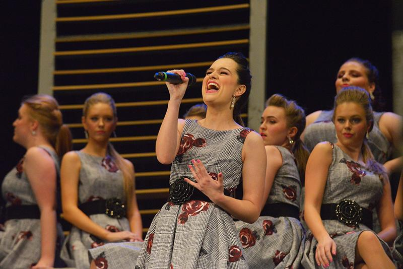"""Senior Maddi Butler belts her solo during the City Lights show, called """"Working for the Weekend."""" """"[The show is] about starting your week at work in an office,"""" Senior Lexie Hayes said. """"We go from working hard to a coffee break to wanting life to slow down to getting paid and then to reaching the weekend."""""""