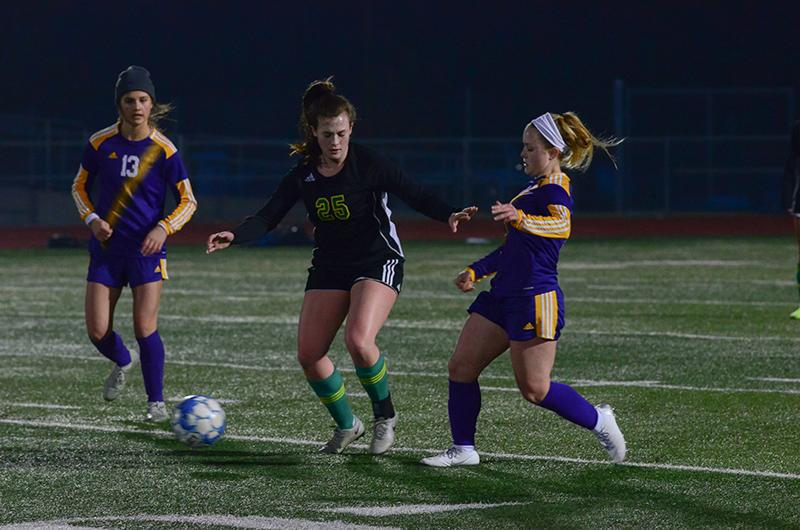 """Senior forward Grace Davis creates space between the ball and an HHS midfielder at the jamboree. """"The jamboree is important for the team because it's the first time we'll all get to really play together and get an idea of what our team is going to look like this year,"""" Davis said. """"Hopefully we also use it as an opportunity to come out and show the other teams the kind of competition we're gonna be this season."""""""
