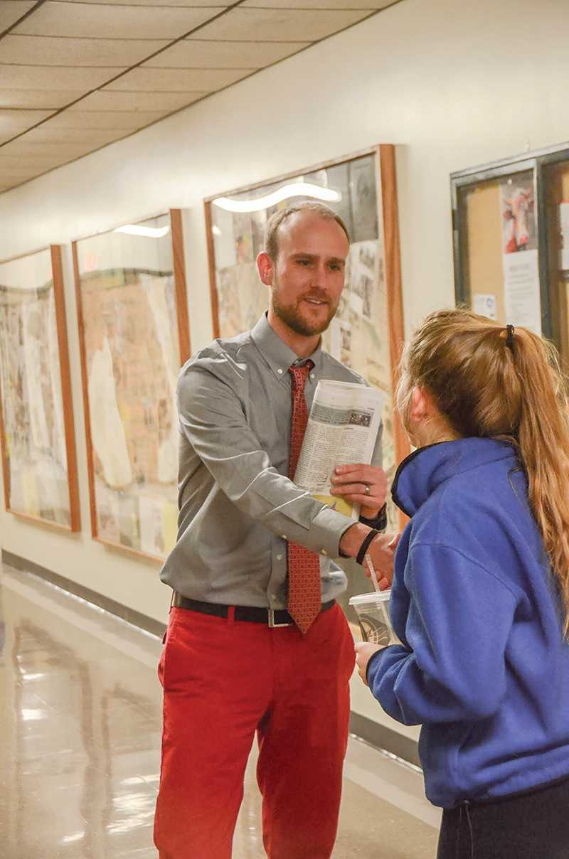 Junior Audrey Snyder greets him in the hall on her way out from working on art. Photo by Allie Pigg