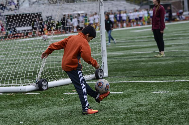 13-year-old Travis Peng balances the ball on his foot waiting to watch his sister, junior midfielder Natalie Peng, play. Travis Peng is a regular ball boy for the Bruins and is a soccer player as well.