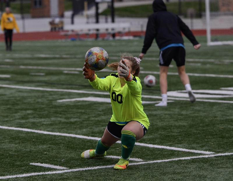 """Sophomore midfielder Hannah Juengermann warms up at halftime to takeover as goalie in the second half after junior goalie Morgan Boussad's injury in the first. """"I've always wanted to play [goalie] but unfortunately after fifth grade I didn't grow as much as everyone else,"""" Juengermann said. """"But I always jumped in and did goalie drills with the keepers."""""""