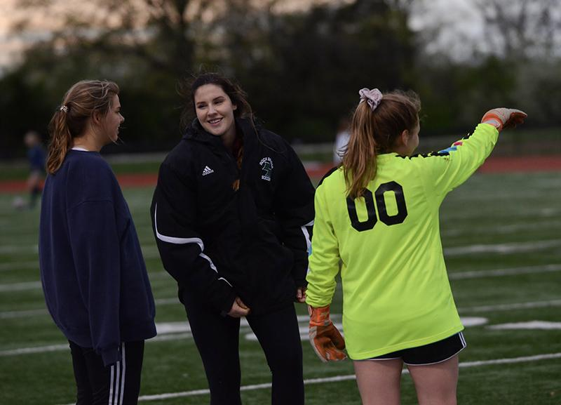 """Assistant Coach Becca Sturgess lightens tensions at halftime with injured goalie Boussad and Juengermann, her substitute. After Boussad hyperextended her elbow, Juengermann said they are all hoping for """"a fast and speedy recovery."""""""